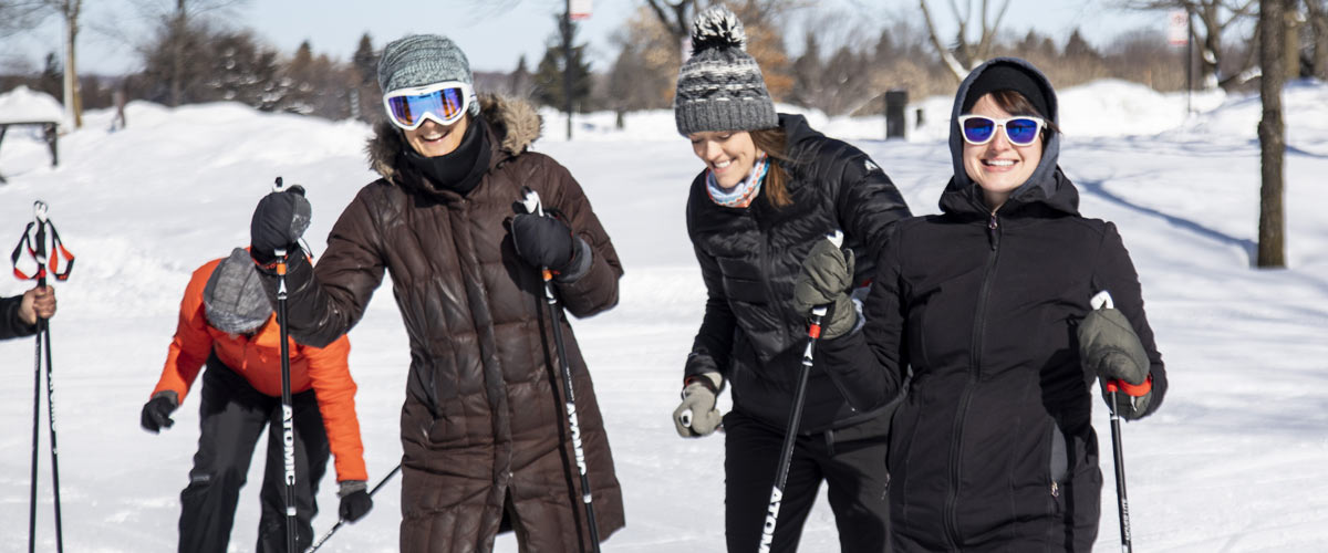 Three women smile while skiing.