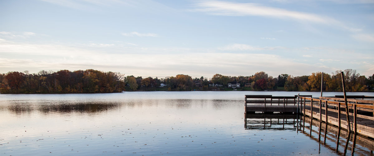 A wooden fishing pier floats on a lake in the fall.
