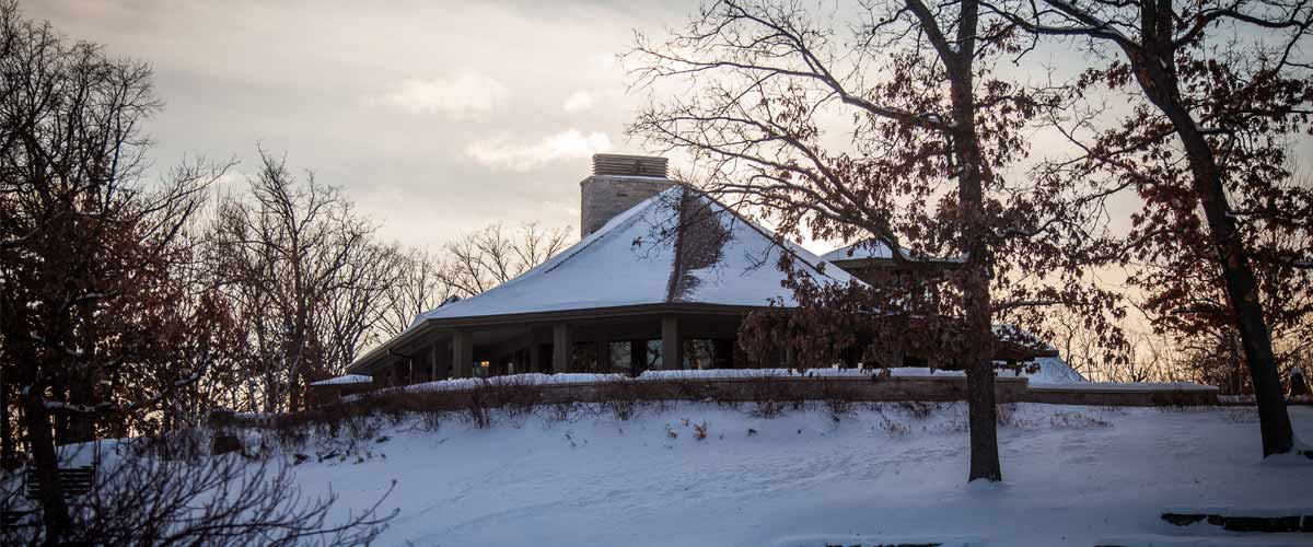 A circular visitor center is silhouetted by sunset on a snowy day.