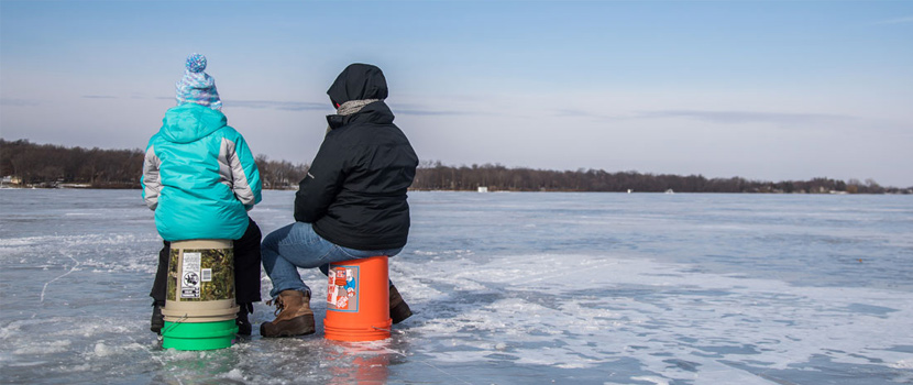 Two people sit on buckets on a frozen lake to ice fish.