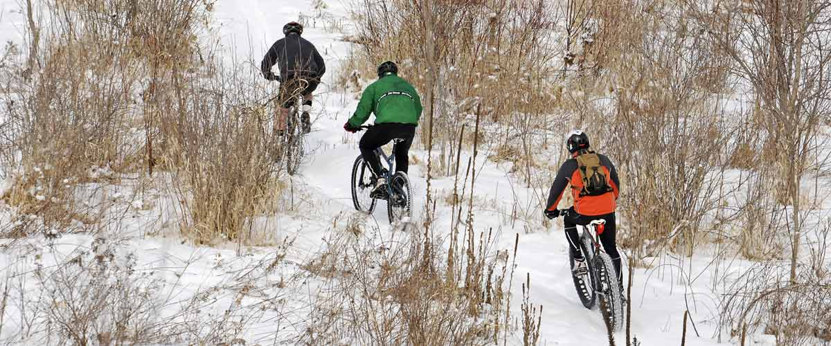 Three mountain bikers on a snowy trail.