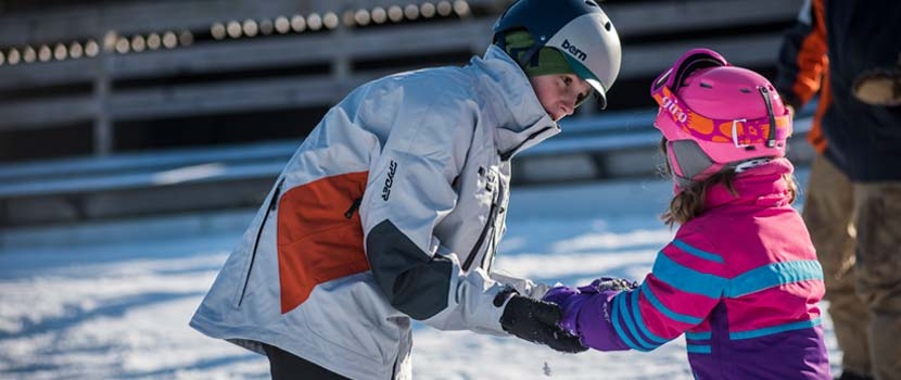 A ski instructor helps a young girl learn how to ski.
