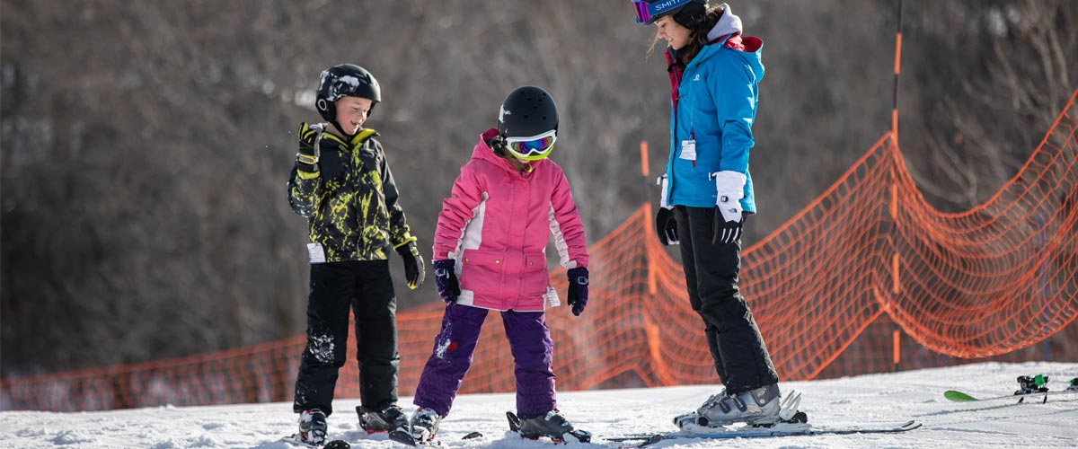 A ski instructor teaches two young kids how to downhill ski.