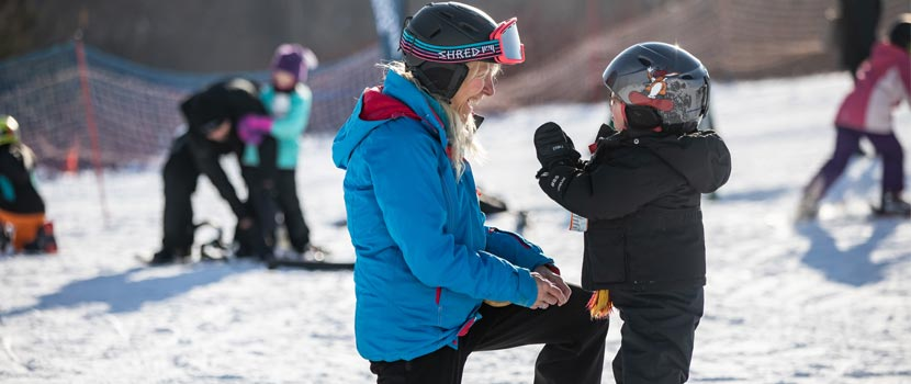 A woman ski instructor teaches a young boy how to downhill ski.