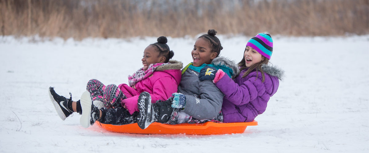 Three girls smile after sledding down a hill.