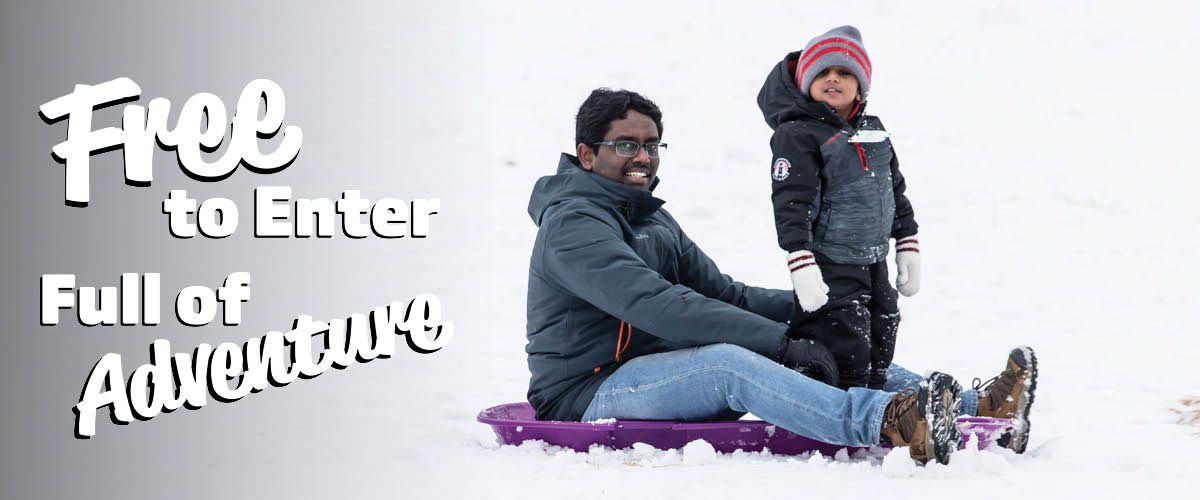A man and a boy smile after sledding down a hill.