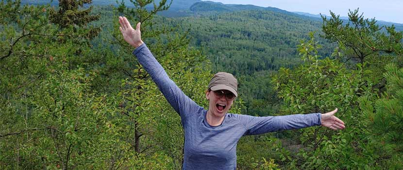A woman spreads her arms out wide and smiles and she stands on top of a mountain.