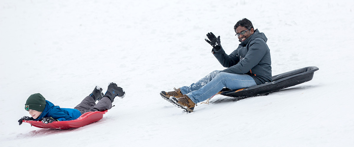 two people sledding down a snowy hill