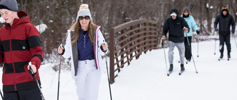 Several people cross-country ski over a bridge.
