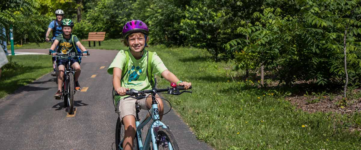 A boy smiles as he bikes down a paved trail.