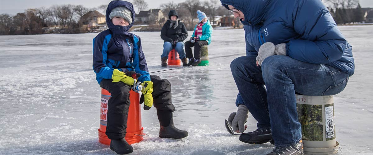 A boy and his father go ice fishing.