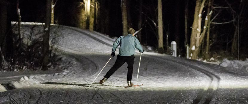 A person skis down a lit trail at night.