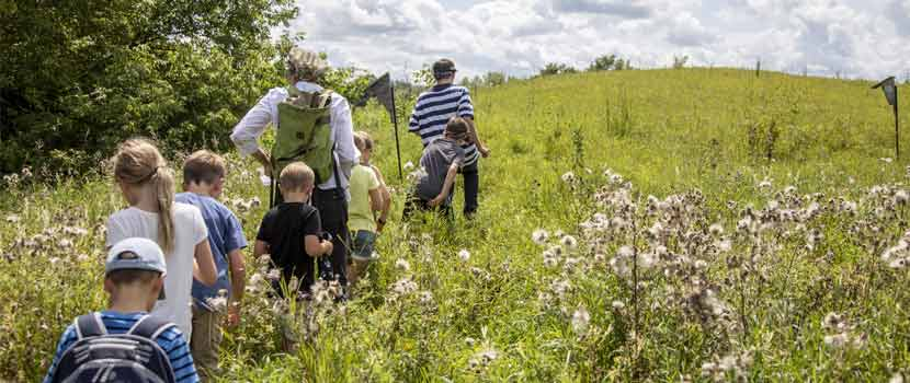 Kids follow an instructor into a prairie.