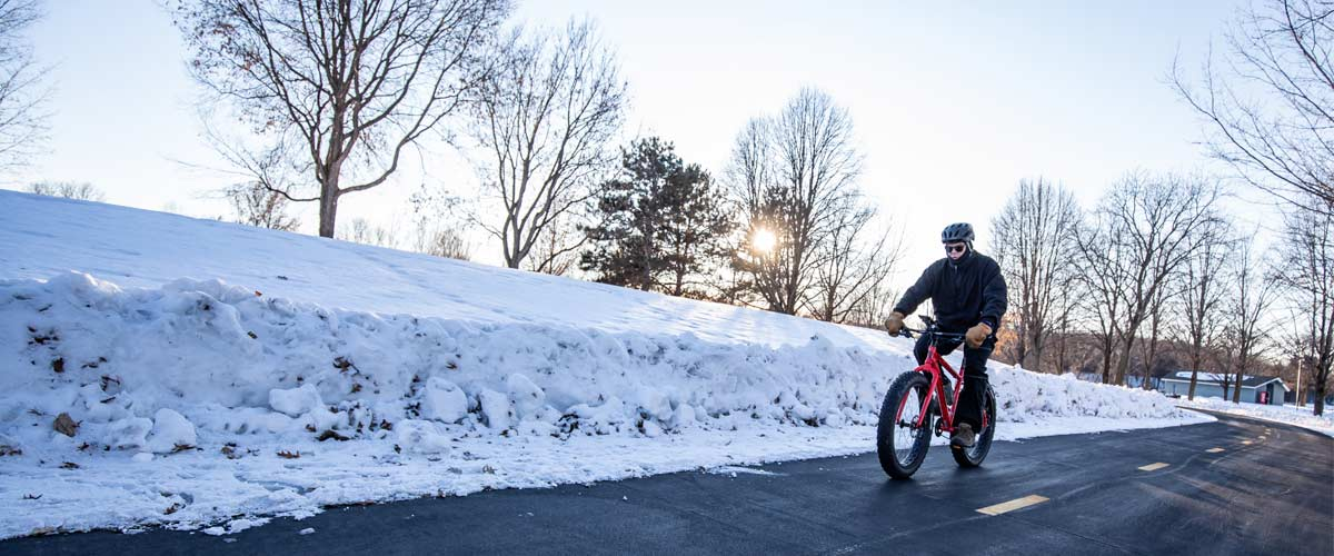 A person bikes down a paved trail in the winter.