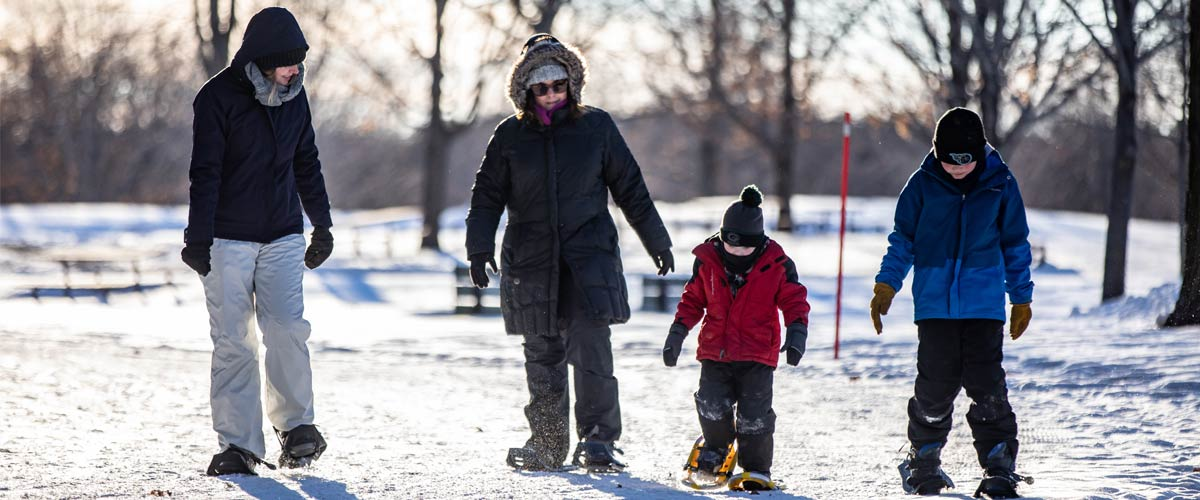 A family goes snowshoeing together.
