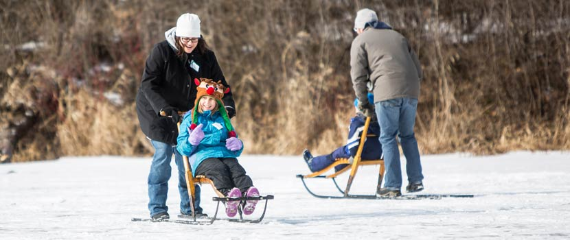 A woman pushes a child in a kicksled across a frozen lake.