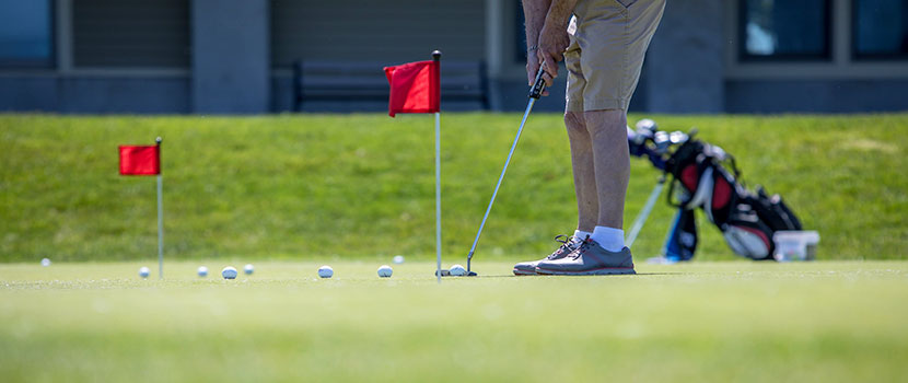 A person squares up to putt a golf ball.