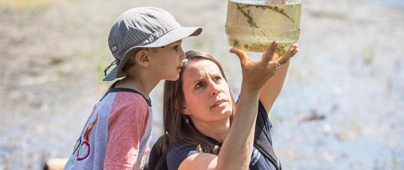 A naturalist shows a jar of pond water to a young boy.