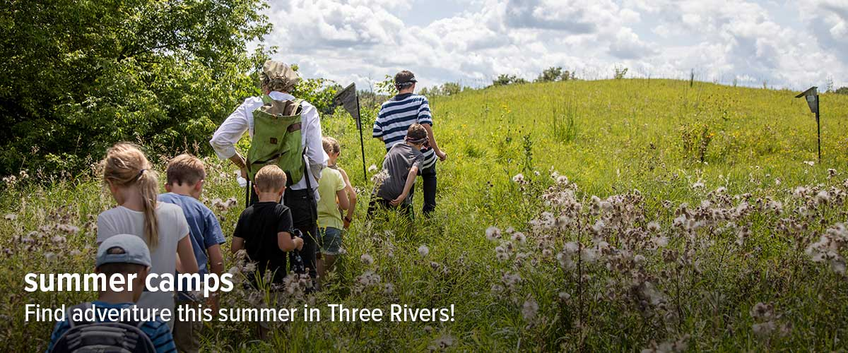 A group of kids follows a camp leader into a blooming prairie.