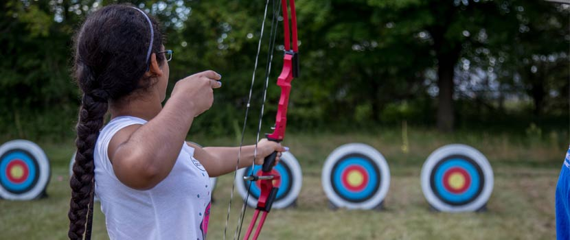 A woman aims a bow and arrow at a target.
