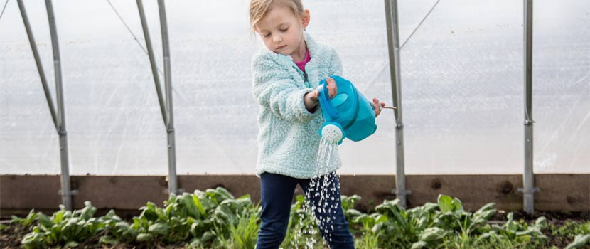 A young girl waters plants in a greenhouse.