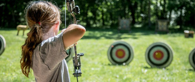 A girl aims a bow and arrow at a target.
