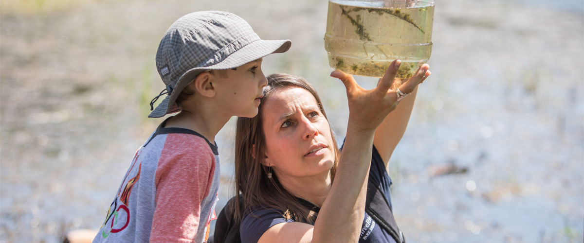 A naturalist shows a boy a jar of pond water.