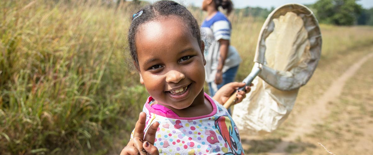 A girl holds a butterfly net and smiles at the camera.