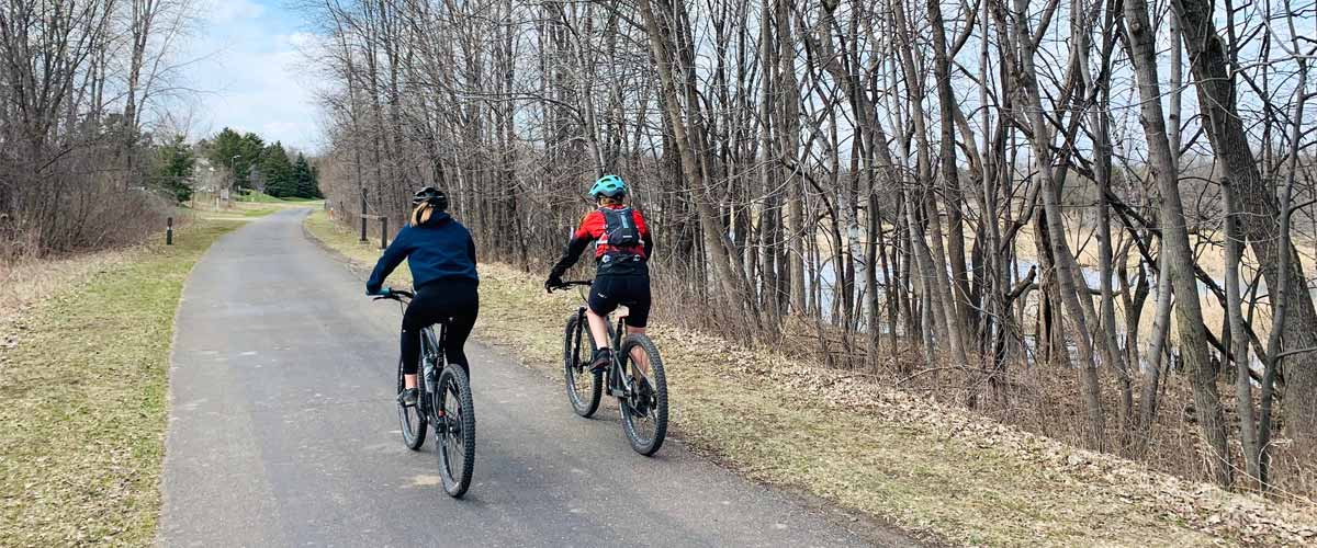 Two bikers ride down a paved trail along a river.