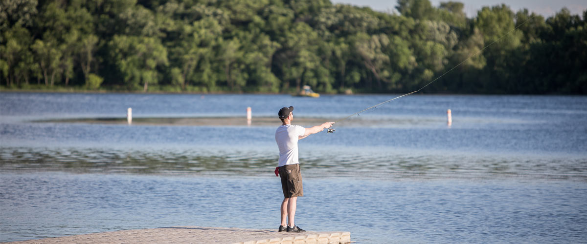 A man casts a fishing line from a pier.