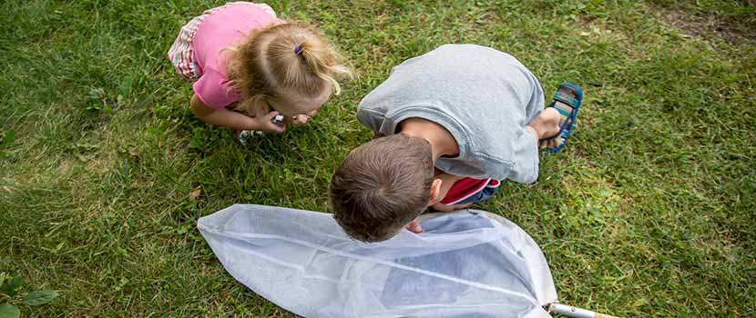 Two kids examine a net on the ground.
