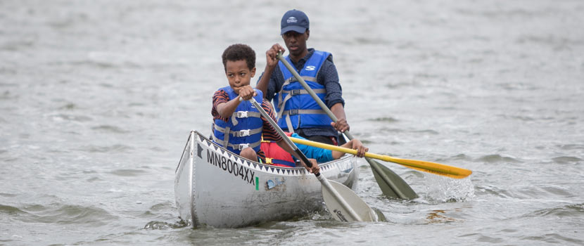 A boy and an adult paddle a canoe.