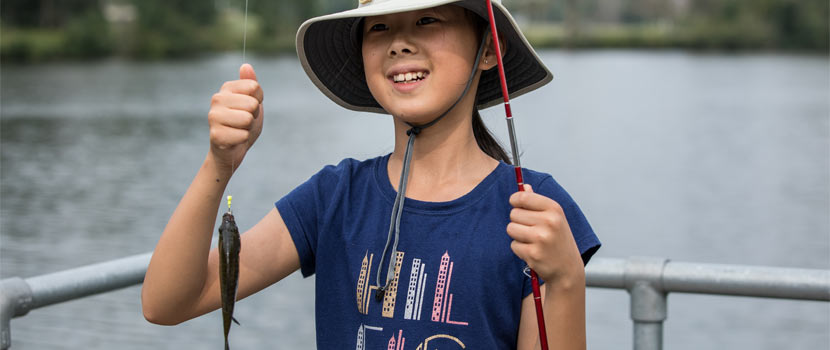 A girl smiles as she holds up a fish she caught.