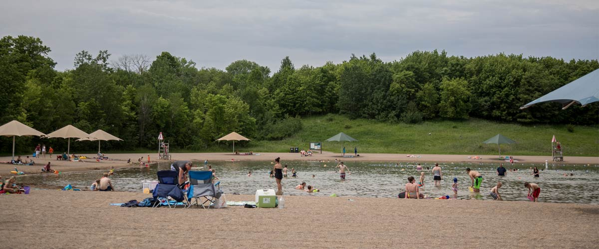 People lounge around the edge of a sandy swim pond on a cloudy day.