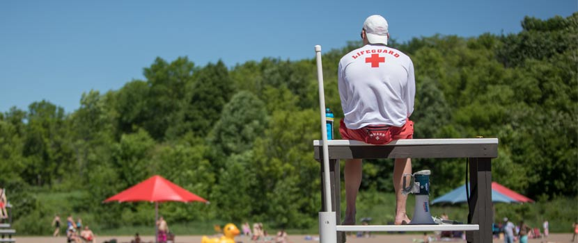 A lifeguard watches over a swimming area from a chair.