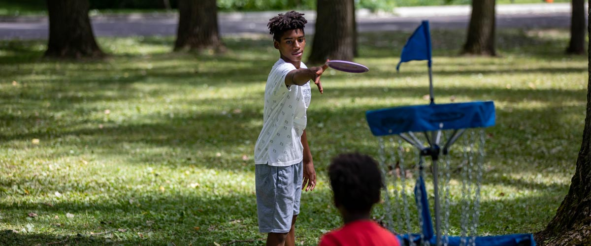 A boy tosses a disc toward a disc golf basket on a summer day.