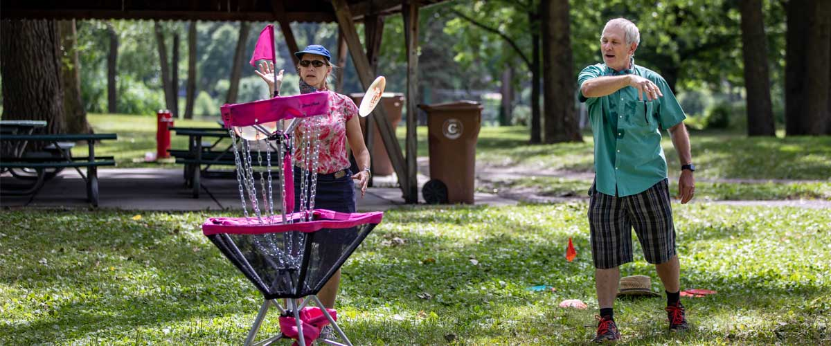 An older man and woman aim their discs at a basket.
