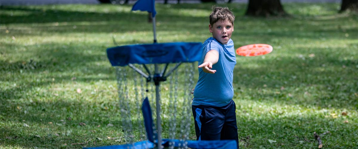 A young boy tosses a disc toward a basket.