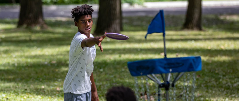 A boy aims a disc at a disc golf golf basket.