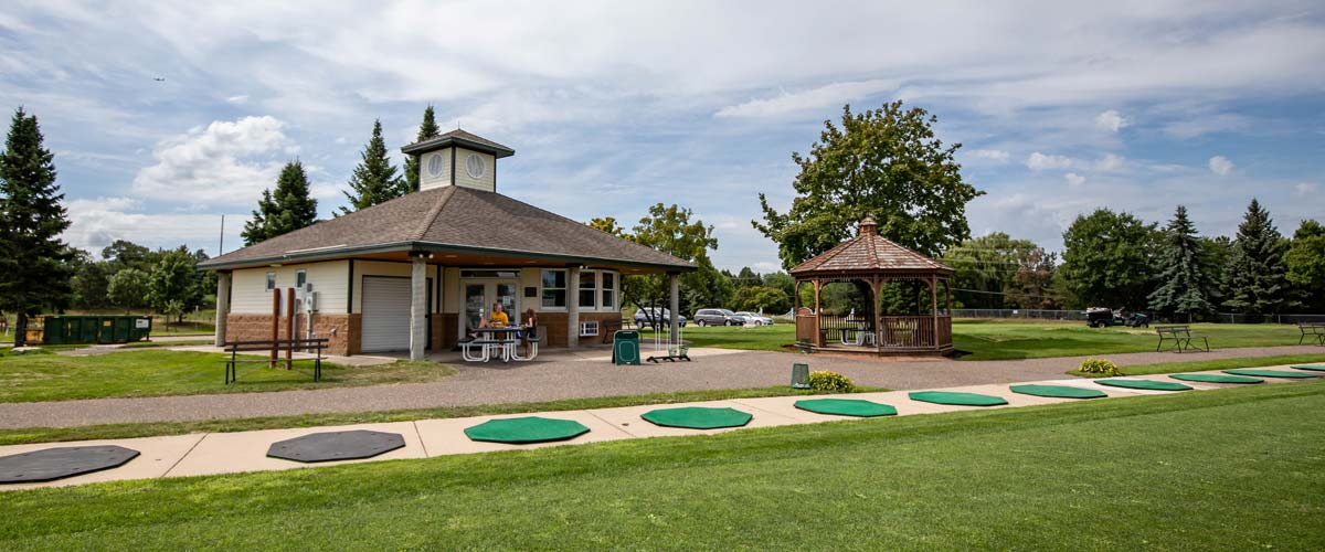 A small clubhouse and gazebo sit behind a row of tee pads at a driving range.