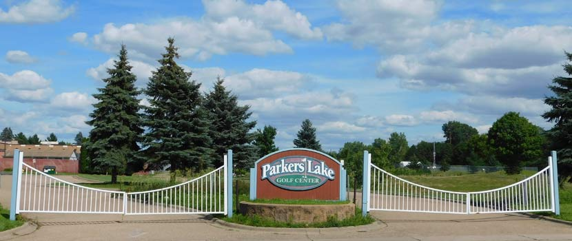 The entrance sign of Parkers Lake Golf Center with tall pine trees in the background.