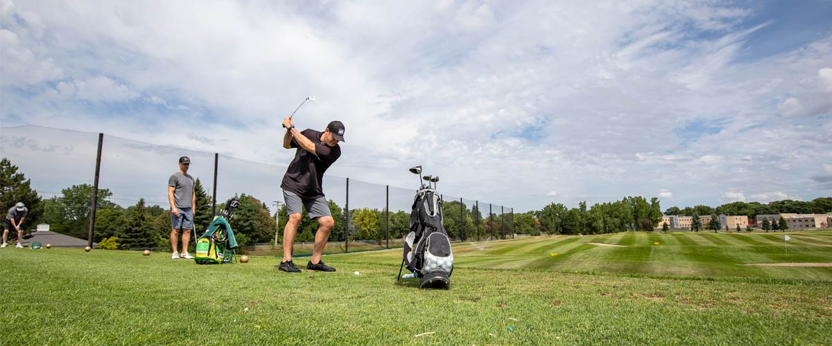 A man practices his swing at a driving range.