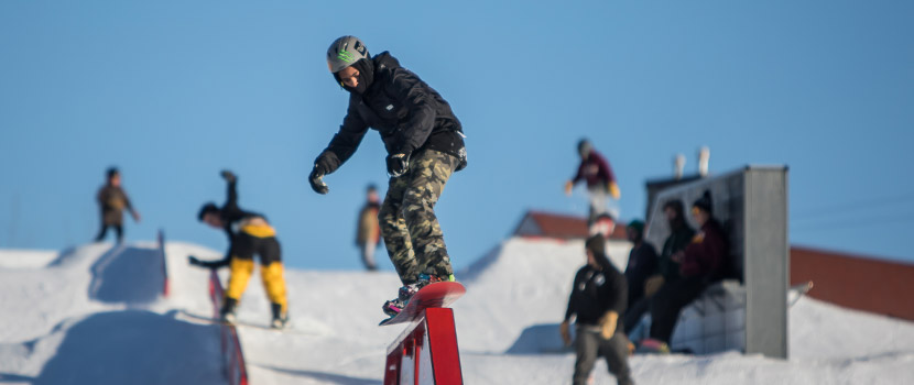 A snowboarder rides over a pipe feature. Several others snowboarders are behind him.