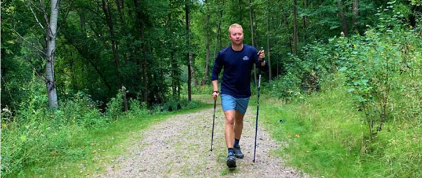 A man walks on a wooded trail using walking poles.