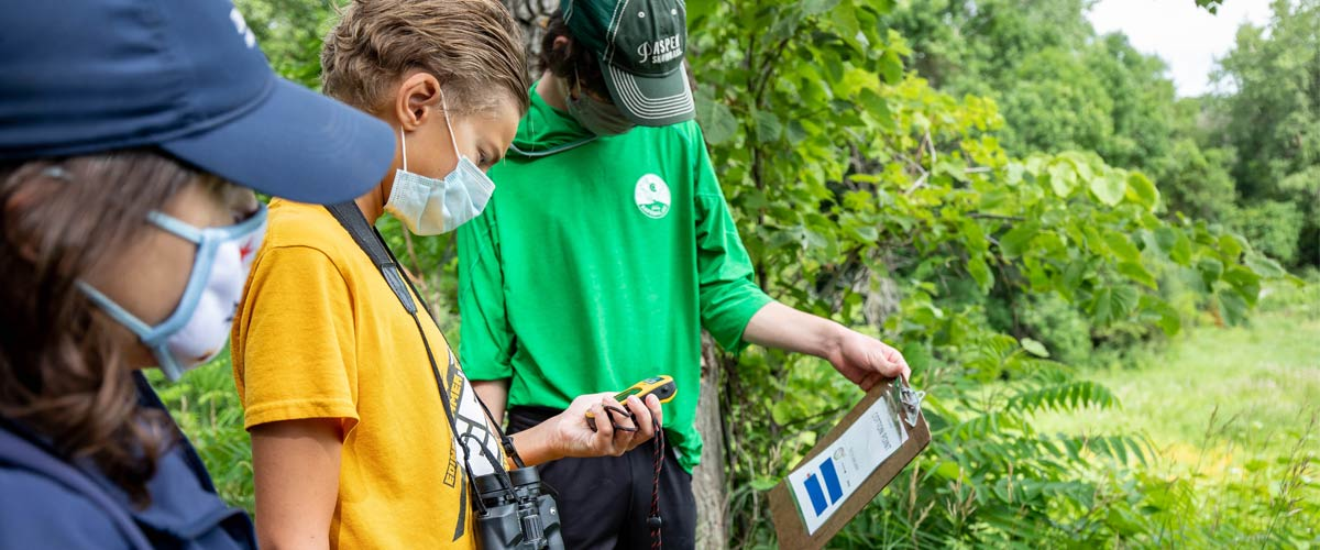 Two middle school-aged boys and a naturalist read a clipboard and use a GPS unit outside.