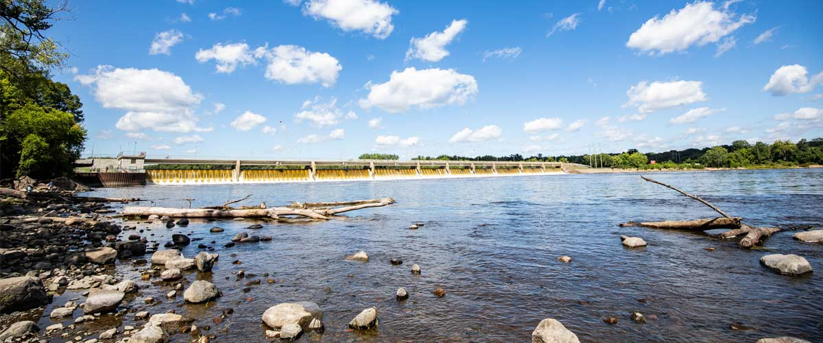 The Mississippi River flows over the Coon Rapids Dam on a sunny summer day.