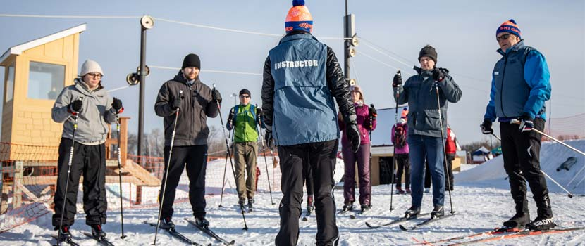 An instructor teaches a small group of people how to cross-country ski.