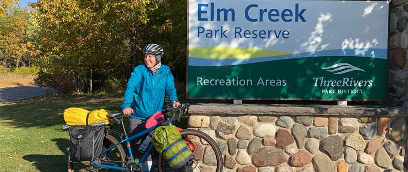 A woman stands in front of the Elm Creek Park Reserve sign with a bike packed for camping.