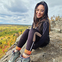 annabella lau sitting at an overlook of fall forests