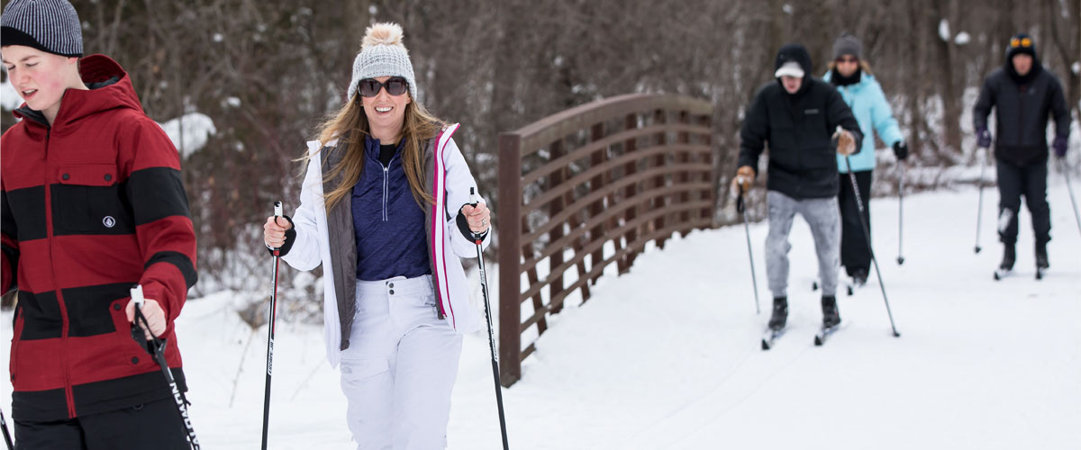 Several cross-country skiers cross a bridge in the winter.
